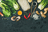 Asian cuisine ingredients over dark slate stone background, vegetables, spices, shrimp, rice, sauces for cooking vietnamese, thai or chinese food