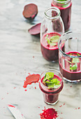 Fresh morning beetroot smoothie or juice in glasses with mint leaves, grey marble background, copy space