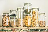 Getreide, Nudeln, Hülsenfrüchte und Mandeln in Vorratsgläsern auf Holztisch
