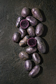Raw purple uncooked organic potatoes, whole and sliced over dark texture background