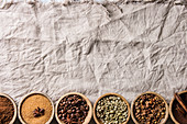 Variety of grounded, instant coffee, different coffee beans, brown sugar, spices in wooden bowls in row over white linen textil as background