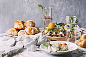 Easter table setting with colored orange eggs, hot cross buns, green branches decorated, empty white plate with cutlery, glass of lemonade drink
