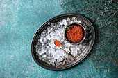 Bowl of red caviar on vintage metal tray with ice over turquoise texture background