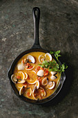 Vongole in tomato cream sauce for pasta in cast-iron pan over old metal texture background