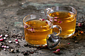 Two glasses of hot tea, rose buds, heart shaped tea strainer, pink sugar over old dark metal background