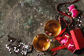 Valentinstag: Zwei Tassen Tee mit Rosenblüten daneben Herzplätzchen in Geschenkschachtel