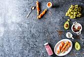 Breakfast set with smoked salmon on crispy breadsticks, yogurt, smoothie, avocado, muesli, milk, berries and green grape