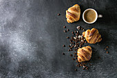 Fresh baked traditional croissants and mug of espresso coffee, coffee beans, sugar over black texture background