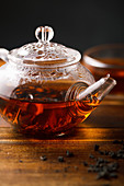 Transparent glass tea pot with hot black tea on wooden table