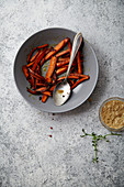 Flatlay image with roasted caramelized carrots with olive oil and honey sauce in gray bowl on textured background