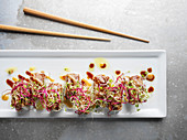 Colorful roll of sushi on rectangular white plate on rustic metal surface