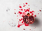 Half pomegranate on a white textured surface with pomegranate juice splashed around