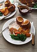 Sunday roast dinner of chicken with vegetables gravy and yorkshire puddings