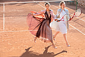 Brünette Frau im Abendkleid mit Tüllbahnen und blonde Frau in weißem Tüllkleid und Jacquardmantel auf Tennisplatz