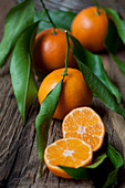 Mandarins with leaves on a wooden surface