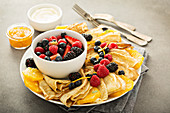 Thin crepes with fresh fruit and berries served with orange marmalade and cream cheese spread