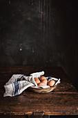 Frische Eier auf Geschirrtuch in Keramikschale