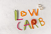 The phrase 'low carb' written in vegetable sticks
