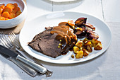 Horse shoulder Sauerbraten (marinated pot roast) with fried potatoes and apples