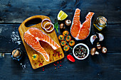 Two steaks of salmon with fresh ingredients for tasty cooking on rustic wooden background, top view, banner