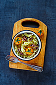 Food background with tasty light pasta salad, fresh raw tomatoes and olives in vintage bowl over grunge table