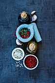 Top view of olive oil, balsamic vinegar, mortar and pestle with various colorful spices on dark grunge background