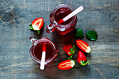 Top view of summer drink with strawberry in glass jar on the vintage wooden background