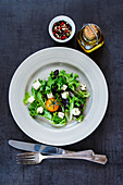 Delicious colorful salad with yellow tomatoes and feta cheese on vintage background