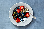 Oat flakes, berries with yogurt and seeds for breakfast on plate over grey vintage background