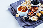 Close up of tasty breakfast background with oat flakes, honey, berries and nuts on white vintage kitchen table