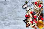 Colorful ingredients for cooking breakfast or smoothie (fresh berries, nuts, oat flakes, dried fruits, chia seeds and honey) over concrete textured background
