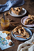 Slices of a rustic apple pie with walnuts and caramel sauce