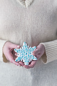 Woman holding gingerbread snowflake cookie