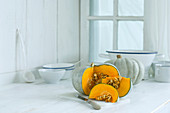 A sliced Crown Prince pumpkin on a kitchen counter