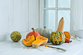 Various pumpkins on a rustic kitchen counter