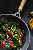 Flower sprouts with tomatoes and pine nuts in a pan