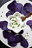 Purple potato chips, tzatziki dip and chives on a white marble board