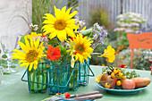 Sonnenblumen, Kapuzinerkresse und Bienenweide in Gläsern