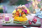 Herbst-Strauß aus Rosen und Heide in Kürbis als Vase