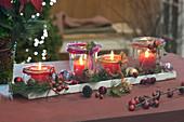 Einmachgläser auf Untersetzer als Adventskranz dekoriert
