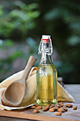 Almond oil in a flip-top bottle and almonds on a wooden table