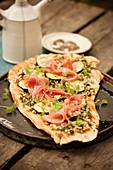 Pizza mit Pesto, Prosciutto und Zucchinischeiben