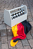 A grey beer bottle carrier with a German flag