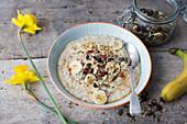 Breakfast Bowl mit Porridge, Bananen und Kürbiskernen