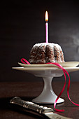 A mini chocolate cake with a candle on a cake stand