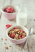 Homemade crunchy muesli with candied hibiscus flowers and grain milk
