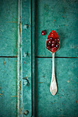 Cornelian cherry jam on a spoon with Cornelian cherries