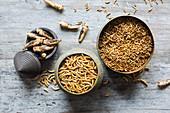 Essbare gefriergetrocknete Heuschrecken, Mehlwürmer und Buffalowürmer auf Holzuntergrund