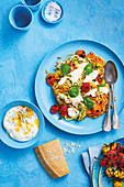 Rainbow courgetti with balsamic roast tomatoes and buratta topped with pine nuts and basil leaves