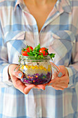 Salad for work in a jar cherry tomatoes chicken lettuce woman holding a jar with salad lunch